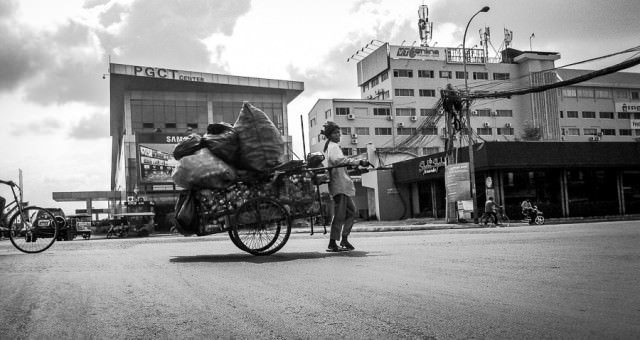 A woman pulls her cart of wares across the intersection in Phnom Penh, Cambodia.