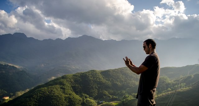 Adrian taking a photo with his iPhone over the valley outside Sapa, Vietnam.