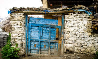 A wooden gate set in a rock wall in Muktinath, Nepal.