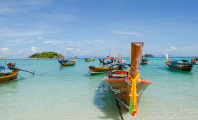 Long tail boats lined up on the beach of Koh Lipe, Thailand.