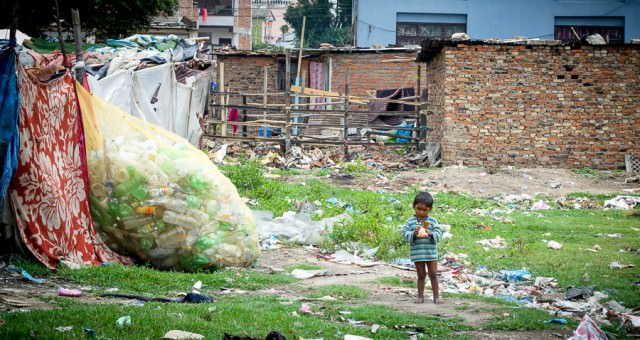 Young girl standing in a field littered with garbage.