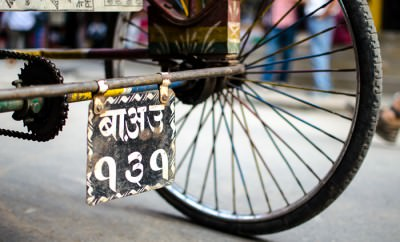 The wheel of a rickshaw and a Nepal license plate.