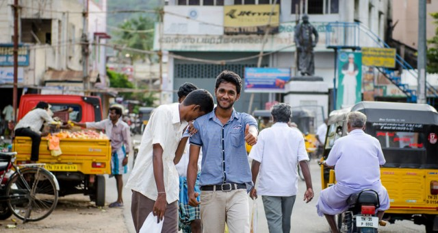 Two young men walk down the street in Tiruvannamalai, one gives a thumbs us.